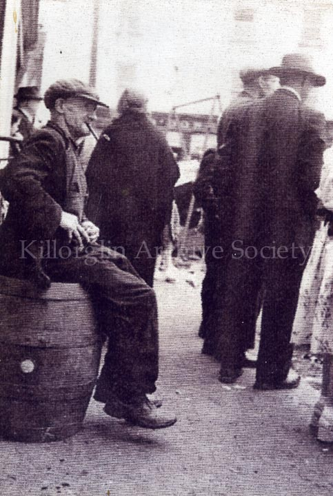 Man sitting on an old Guinness Barrel smoking a pipe during Puck Fair, circa 1950's