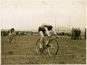 Gene Mangan winning a spint cycleing race in a field