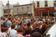 The crowd gather for the arrival of King Puck on to the Puck Fair Stand. Note Doyle's Draper and Champs Off Licence which have since been knocked. 1990s.